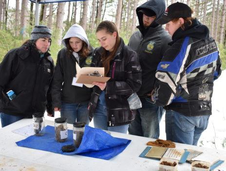 Students gather around an identification station.