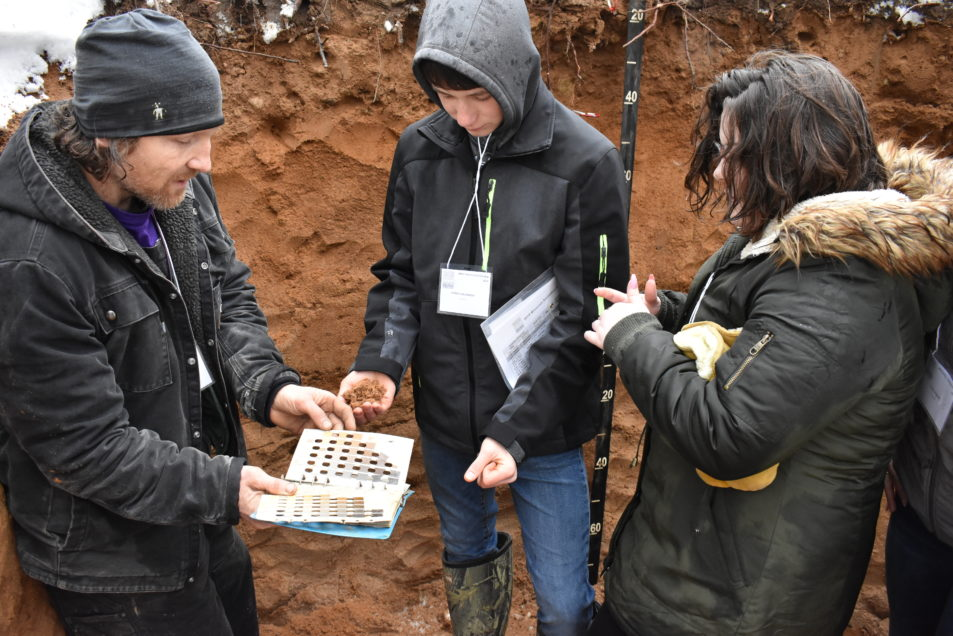 Students stand in a soil pit.